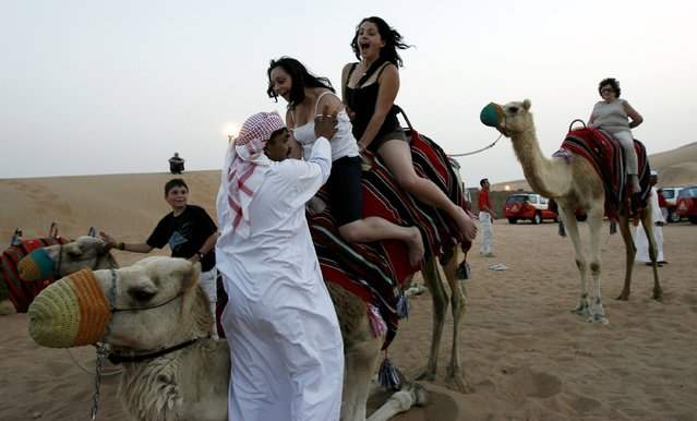 A keeper helps tourists dismount from a camel in the Dubai desert April 10, 2007 file photo. (Photo by Ahmed Jadallah/Reuters)