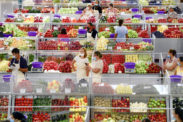 Fruit and vegetable vendors, wearing masks against the spread of the COVID-19 infections, wait for customers at a market in Bucharest, Romania, Tuesday, August 11, 2020. Romania is faced with an increasing number of COVID-19 infections and related deaths over the past weeks, the highest levels since the pandemic started in the country in February, blamed mostly on people not observing the prevention regulations, like correctly wearing a face mask. (Photo by Andreea Alexandru/AP Photo)