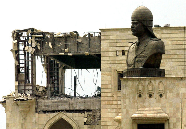 A statue of Iraqi President Saddam Hussein, at his palace, damaged during a U.S. led air strike in Baghdad, on March 23, 2003. (Photo by Faleh Kheiber/Reuters/The Atlantic)