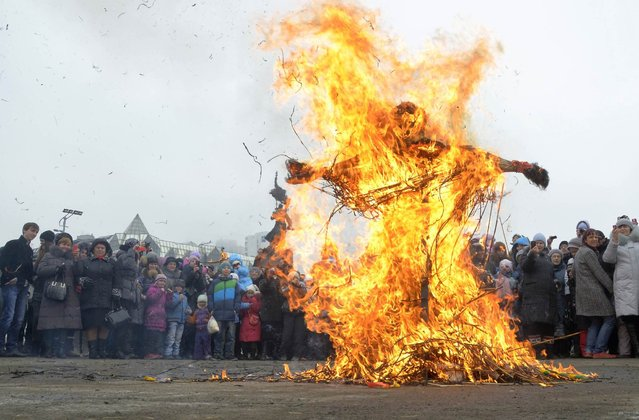 People burn an effigy of Lady Maslenitsa as they celebrate Maslenitsa, or Pancake Week, in the Russian far eastern city of Vladivostok, March 17, 2013. Maslenitsa is widely viewed as a pagan holiday marking the end of winter and is celebrated with pancake eating, while the Orthodox Church considers it as the week of feasting before Lent. (Photo by Yuri Maltsev/Reuters)