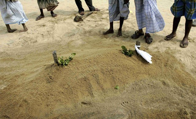 Muslims stand and pray at the grave of a young girl buried on Kalmunai beach following the December 26 tsunami on Sri Lanka's east coast in this January 7, 2005 file photo. (Photo by Kieran Doherty/Reuters)