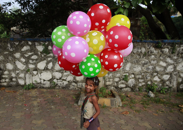 Lali carries balloons to sell on a beach in Mumbai, India, Sunday, October 11, 2015. The United Nations General Assembly marks October 11 as the International Day of the Girl Child, to recognize girls' rights and the unique challenges girls face around the world. (Photo by Rafiq Maqbool/AP Photo)