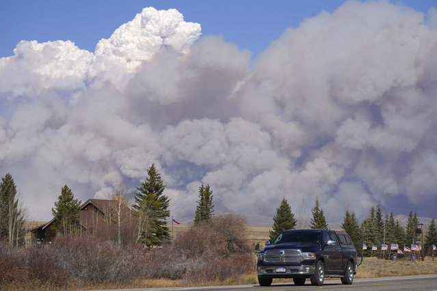 Smoke rises from mountain ridges as a motorist heads eastbound on Highway 34 while a wildfire burns Thursday, October 22, 2020, near Granby, Colo. (Photo by David Zalubowski/AP Photo)