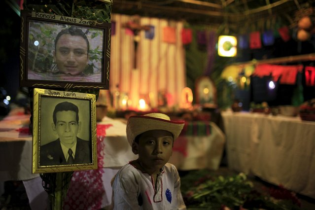 """A child stands at a family altar during the celebration of """"Los Canchules"""" in Nahuizalco November 1, 2015. (Photo by Jose Cabezas/Reuters)"""