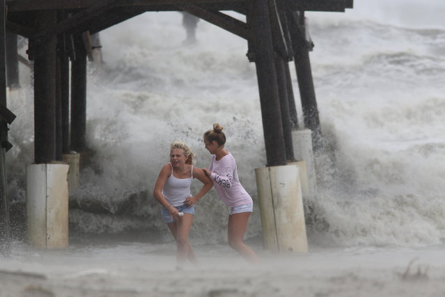 Cocoa Beach, Florida, USA. 7th October, 2016. Kaleigh Black, 14, left, and Amber Olsen, 12, run for cover as a squall with rain and wind pelt them while they explore the Cocoa Beach Pier on Friday (10/7/16) after hurricane Matthew passed to the east on Florida's east coast.(Photo by Douglas R. Clifford/Tampa Bay Times/ZUMA Wire/Alamy Live News)