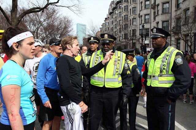 Runners talk to Boston Police near Kenmore Square after two bombs exploded during the 117th Boston Marathon on April 15, 2013 in Boston, Massachusetts.  (Photo by Alex Trautwig)