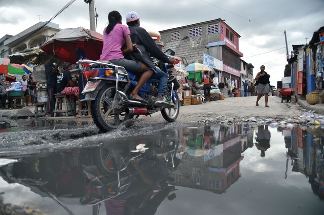 Part of a street is reflected in a puddle near the canal of Portail Leogane, in the Haitian capital Port-au-Prince, on October 1, 2016. (Photo by Hector Retamal/AFP Photo)