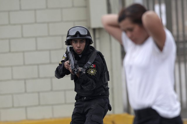 A member of the Fuerza Civil (Civil Force) police unit takes part in a simulated crime situation during a media presentation to show the police model that the federal government wants for the rest of the country, at the police academy in Monterrey December 17, 2014. Fuerza Civil, a tactical team of the police unit trained by the army, was created by the Nuevo Leon government in 2011 to curb down corruption and infiltration by drug gangs in the police corps, local media reported. (Photo by Daniel Becerril/Reuters)