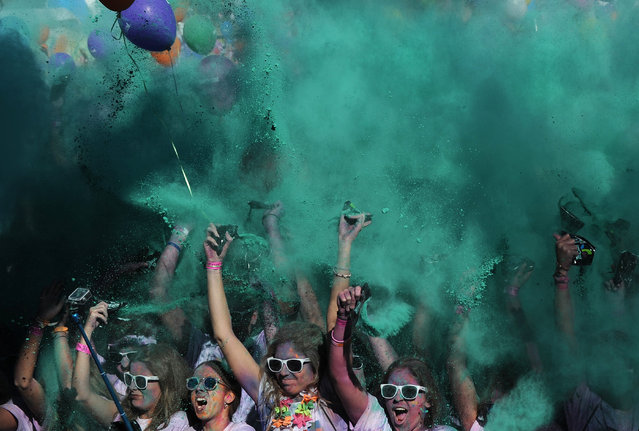 Runners covered in coloured powder dance after taking part in the Color Run of Sevilla on November 8, 2015. The Color Run is a race where participants are showered with colored powder after each kilometer. (Photo by Cristina Quicler/AFP Photo)