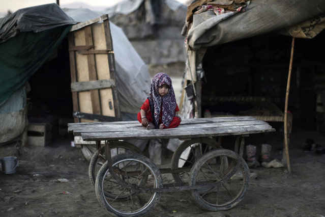 A Pakistani child, whose family was displaced by 2010 floods from a village in Pakistan's Sindh province, sits on a wooden cart outside her family's makeshift home, in a slum on the outskirts of Islamabad, on February 8, 2013. (Photo by Muhammed Muheisen/AP Photo)