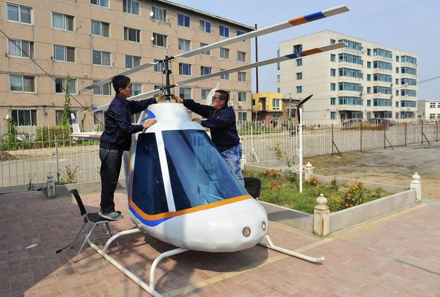 Tian Shengying (R), a 55-year-old blacksmith, adjusts the rotor of the helicopter, in Shenyang, Liaoning province, September 21, 2012. Tian built the bottom, body, tail and rotor of the helicopter single-handedly without a detailed blueprint in just half a month after receiving a request by an unmanned aircraft research centre. (Photo by Sheng Li/Reuters)