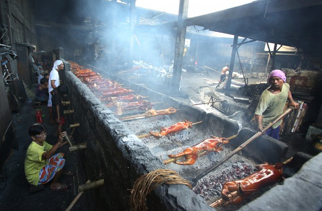 """Filipino workers turn bamboo poles used in pigs at a roasting pit in suburban Quezon city, Philippines on Tuesday, December 23, 2014. Roasted pig is popular during Filipino celebrations and traditionally served during a Christmas eve dinner called """"Noche Buena"""" in this predominantly Roman Catholic nation. (Photo by Aaron Favila/AP Photo)"""