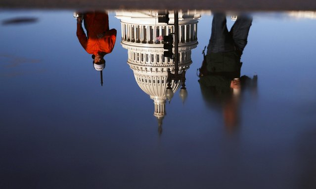The U.S. Capitol building is seen reflected in a puddle in Washington, U.S. November 10, 2020. (Photo by Hannah McKay/Reuters)