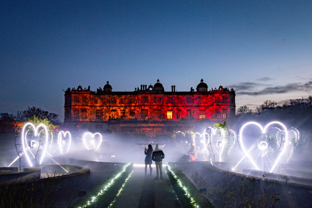 Visitors walk through the gardens at Longleat House, United Kingdom on December 8, 2020, where lights and illuminated structures bathe the grounds in colourful and atmospheric light as part of the Land of Light winter attraction. (Photo by Ben Birchall/PA Images via Getty Images)