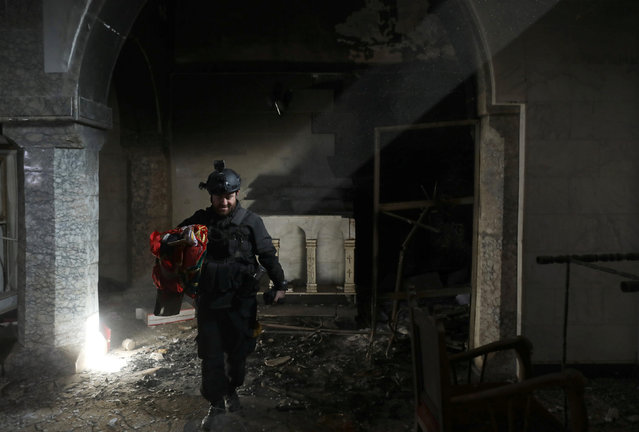 A Christian Iraqi special forces soldier walks in a church in Bartella, east of Mosul, Iraq October 22, 2016. (Photo by Goran Tomasevic/Reuters)