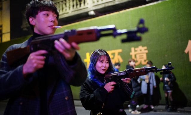 People play with toy guns outside a bar at night, almost a year after the global outbreak of the coronavirus disease (COVID-19) in Wuhan, Hubei province, China on December 11, 2020. (Photo by Aly Song/Reuters)