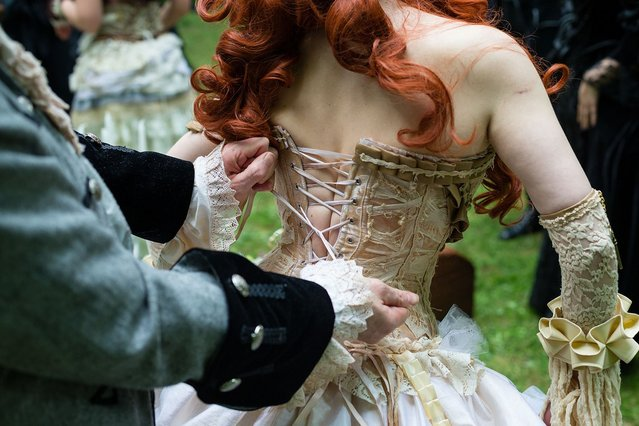 A man helps a woman straightening her corset during the traditional park picnic on the first day of the annual Wave-Gotik Treffen, or Wave and Goth Festival, on May 17, 2013 in Leipzig, Germany. The four-day festival, in which elaborate fashion is a must, brings together over 20,000 Wave, Goth and steam punk enthusiasts from all over the world for concerts, readings, films, a Middle Ages market and workshops. (Photo by Marco Prosch)