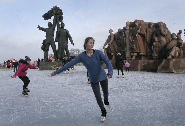"People skate on the rink by a Soviet-era monument of friendship between the Ukrainian and Russian people, in Kiev, Ukraine, Friday, January 2, 2015. Writing on the monument reads: ""Glory to Ukraine!"". (Photo by Efrem Lukatsky/AP Photo)"