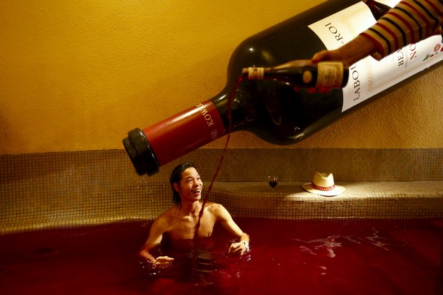A man pours wine into a hot bath with coloured water representing wine at the Hakone Kowaki-en Yunessun spa resort during an event marking Beaujolais Nouveau Day in Hakone west of Tokyo, November 19, 2015. (Photo by Thomas Peter/Reuters)