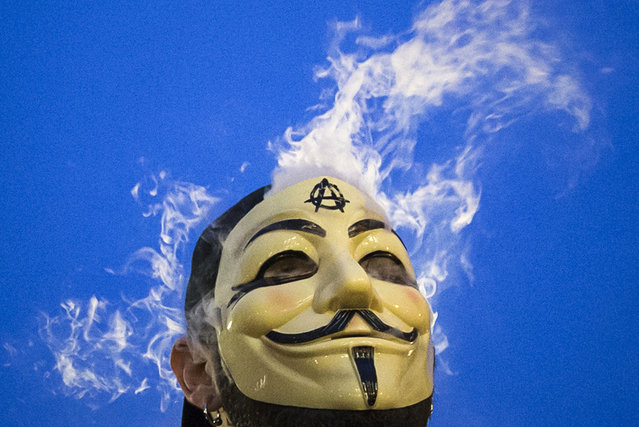 """New York City: Vapor passes through a Guy Fawkes mask as a man smokes while joining supporters of the Anonymous movement who were taking part in the global """"Million Mask March"""" protests in Union Square, New York November 5, 2014. (Photo by Elizabeth Shafiroff/Reuters)"""