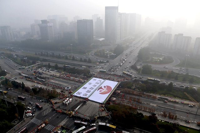 An aerial view shows a new section of the Sanyuan Bridge, part of Beijing's Third Ring Road, on a hazy day in Beijing, China, November 15, 2015. Beijing road maintenance workers started dismantling a 31-year-old bridge on Friday night and replacing it with a new one. The project was scheduled to finished within 24 hours, but was postponed till Sunday due to the poor conditions of the old bridge, local media reported. (Photo by Reuters/China Daily)