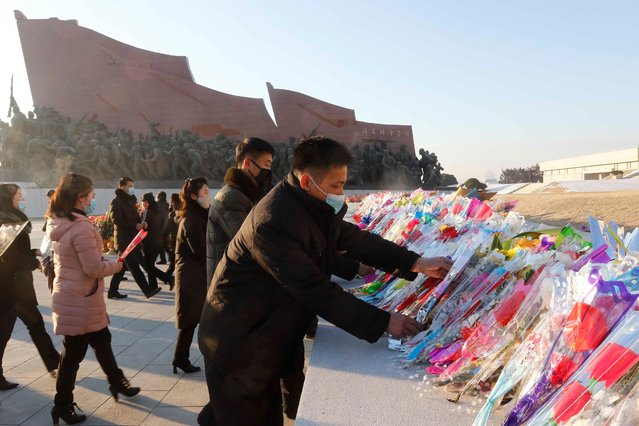 Pyongyang citizens visit Mansu Hill to offer bouquets of flowers to the bronze statues of their late leaders Kim Il Sung and Kim Jong Il on the occasion of the 9th death anniversary of Kim Jong Il in Pyongyang, North Korea, on December 17, 2020. (Photo by Cha Song Ho/AP Photo)