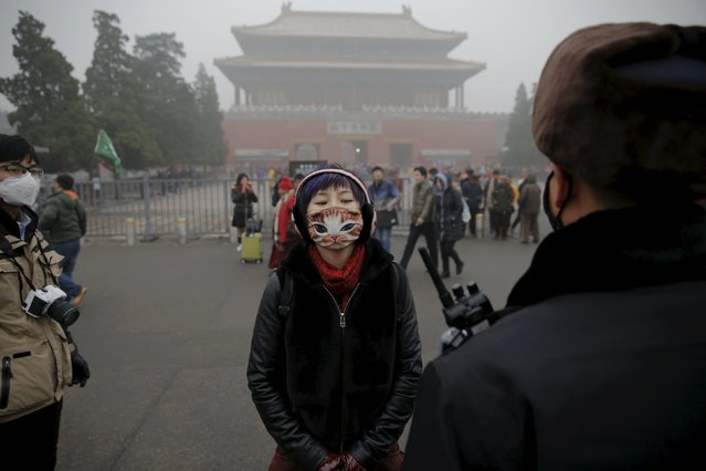 A girl wearing a protective mask talks to a policeman near the Forbidden City on an extremely polluted day as hazardous, choking smog continues to blanket Beijing, China December 1, 2015. (Photo by Damir Sagolj/Reuters)