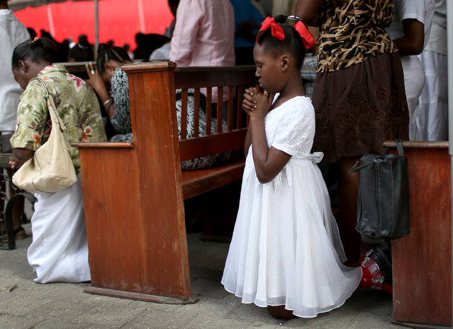 A young girl prays with her family during a service held under tents in place of the Sacré-Coeur church that was destroyed five years ago by a magnitude 7.0 earthquake that struck just before 5 p.m. on Jan. 12, 2010, destroying buildings and killing as many as 316,000 people on January 11, 2015 in Port-au-Prince, Haiti. (Photo by Joe Raedle/Getty Images)