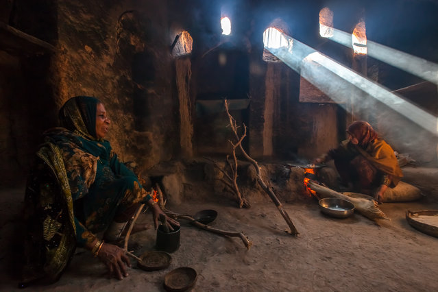 """""""The Bread Makers"""". Two Omani women making traditional arabic bread over an open fire. (Photo and caption by Darryl MacDonald/National Geographic Traveler Photo Contest)"""
