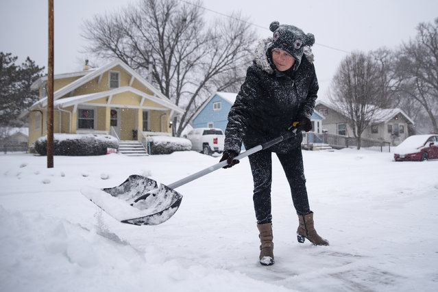 "Wendy Lacina shovels her driveway with a neighbor's help on Monday, January 25, 2021 in Valley Junction, Iowa. Lacina, 53, is scheduled to undergo eye surgery in February. ""Even in this weather, I would always wear my sunglasses. Today I thought, 'It's not sunny out — Let the cold hit the eye, maybe it'll help it"", Lacina joked. ""I got nothing to lose"". (Photo by Olivia Sun/The Des Moines Register via AP Photo)"