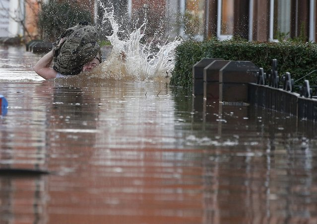 A local resident stumbles as he wades through flood water on a residential street in Carlisle, Britain December 6, 2015. (Photo by Phil Noble/Reuters)