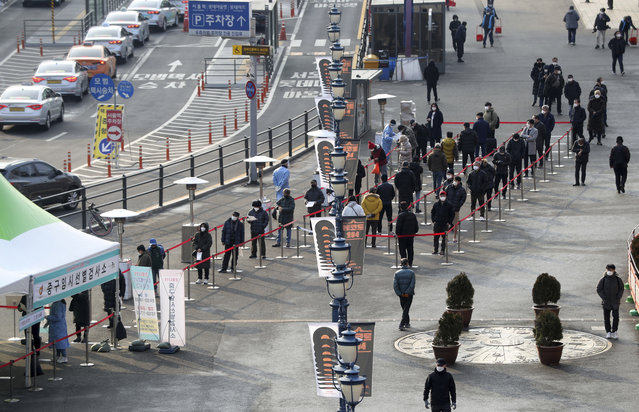 People queue in line to wait for coronavirus testing while maintaining social distancing at coronavirus testing site in Seoul, South Korea, Saturday, December 26, 2020. (Photo by Hong Hyosik/Newsis via AP Photo)