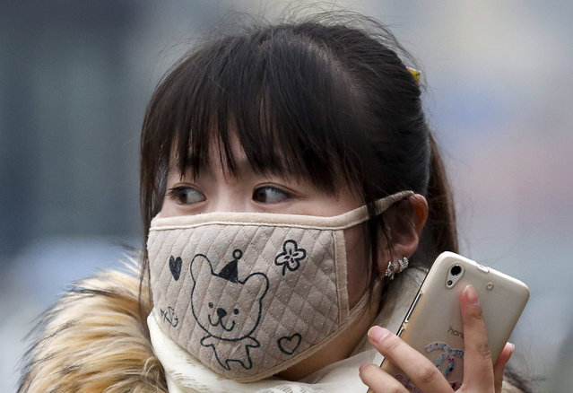 In this December 8, 2015 photo, a woman wears a mask to protect herself from pollutants on a heavily polluted day in Beijing. (Photo by Andy Wong/AP Photo)