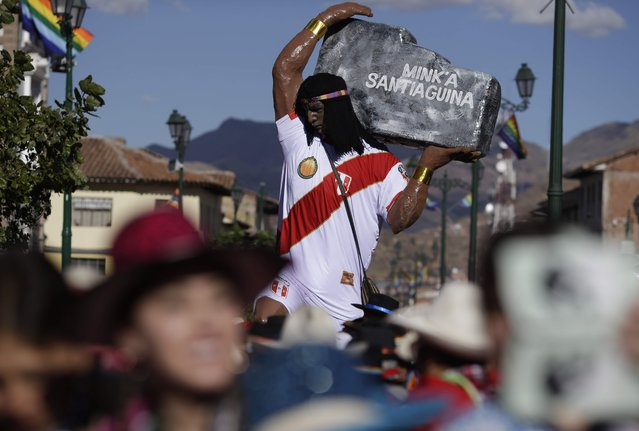 A figure of a man with Peru's national soccer team uniform parades near the Plaza de Armas in Cusco, Peru, Saturday, June 23, 2018. June is full of festivities throughout the region of Cuzco, culminating on June 24 with the Inti Raymi, the Festival of the Sun. (Photo by Martin Mejia/AP Photo)