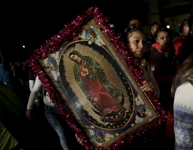 A pilgrim holds up an image of the Virgin of Guadalupe inside the Basilica of Guadalupe during the annual pilgrimage in honor of the Virgin of Guadalupe, patron saint of Mexican Catholics, in Mexico City, Mexico December 11, 2015. (Photo by Henry Romero/Reuters)
