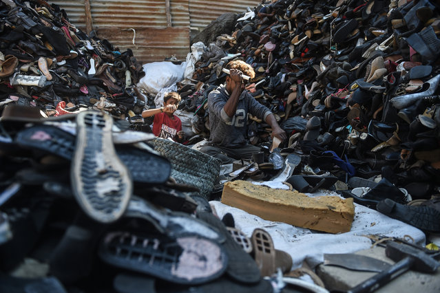 Labourers dismantle old shoes for recycling at a workshop in Karachi on January 13, 2021. (Photo by Rizwan Tabassum/AFP Photo)