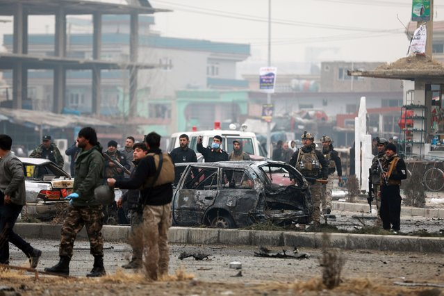 Afghan security personnel inspect the site of a bombing attack in Kabul, Afghanistan, Sunday, December 20, 2020. The strong car bomb explosion rocked the capital Kabul city on Sunday morning, killing multiple people, said a government official. (Photo by Rahmat Gul/AP Photo)