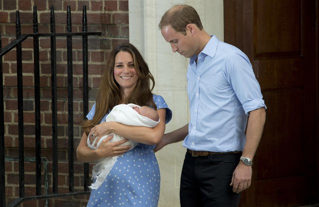 Britain's Prince William, right, and Kate, Duchess of Cambridge hold the Prince of Cambridge, Tuesday July 23, 2013, as they pose for photographers outside St. Mary's Hospital exclusive Lindo Wing in London where the Duchess gave birth on Monday July 22. The Royal couple are expected to head to London's Kensington Palace from the hospital with their newly born son, the third in line to the British throne. (Photo by Joel Ryan/Invision/AP)