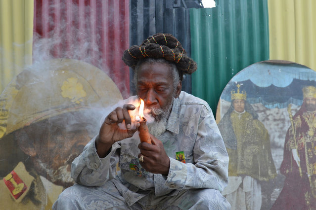 """In this August 28, 2014 file photo, legalization advocate and reggae legend Bunny Wailer smokes a pipe stuffed with marijuana during a """"reasoning"""" session in a yard in Kingston, Jamaica. Jamaica lawmakers on Tuesday, Feb. 24, 2015, passed an act to decriminalize small amounts of pot. (Photo by David McFadden/AP Photo/File)"""