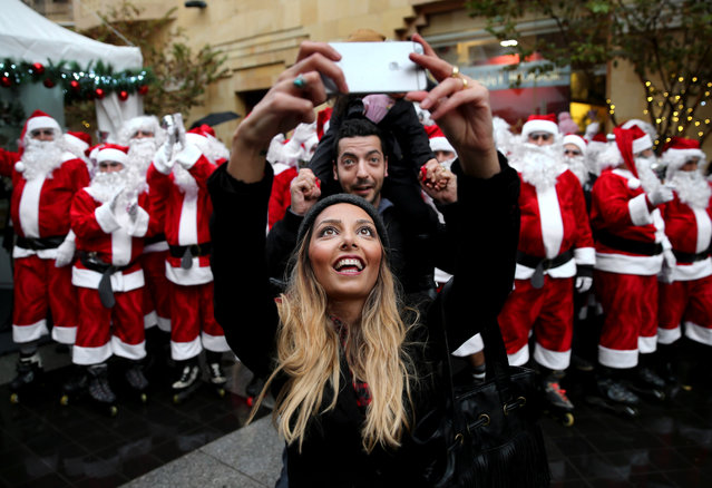 A Lebanese couple take selfie in front men and women wearing Santa Claus costumes during a parade for Christmas, in downtown Beirut, Lebanon, Saturday, December 19, 2015. (Photo by Hussein Malla/AP Photo)