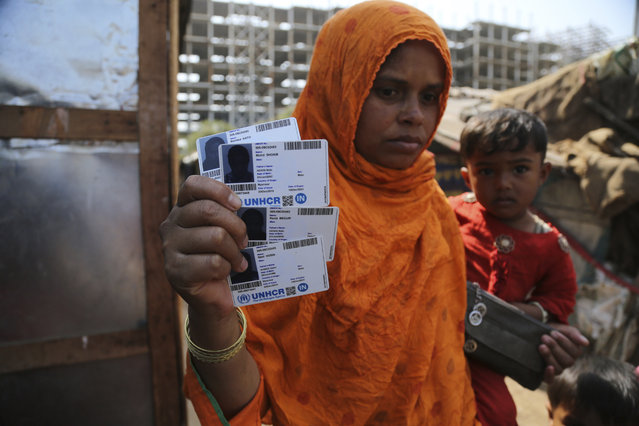 In this March 9, 2021 file photo, Rahima Kato, a Rohingya woman displays identity cards of her family members issued by United Nations High Commissioner for Refugees (UNHCR) at their makeshift camp on the outskirts of Jammu, India. Four Indian states bordering Myanmar have stepped up measures to prevent refugees from entering India through a porous border following last month's military coup in the Southeast Asian country, a government official said Saturday. (Photo by Channi Anand/AP Photo)