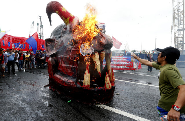 Protesters burn an effigy of President Rodrigo Duterte prior to marching towards the Philippine Congress to coincide with his third State of the Nation Address (SONA) Monday, July 23, 2018 in suburban Quezon city northeast of Manila, Philippines. The protesters assailed Duterte allegedly for failing in his promises to alleviate poverty as well as his so-called war on drugs which saw the killings of thousands, mostly the poor. (Photo by Bullit Marquez/AP Photo)