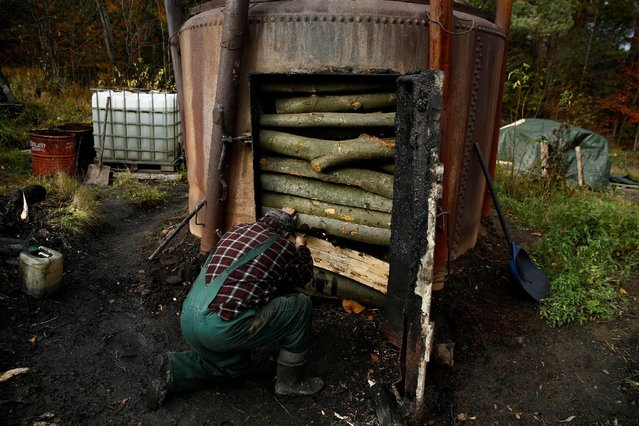 Charcoal burner Zygmunt Furdygiel fires wood inside a charcoal furnace at a charcoal making site in the forest of Bieszczady Mountains, near the village of Baligrod, Poland October 27, 2016. (Photo by Kacper Pempel/Reuters)