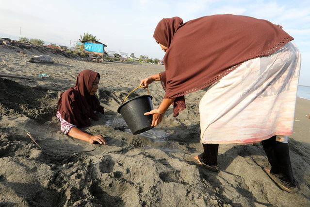 Rumiati, 65, who suffered a stroke, sits in the sand receiving a traditional medical treatment with black sand at Syiah Kuala beach, Banda Aceh, Indonesia, 26 February 2021. Locals in the area believe that bathing with black sand can cure and prevent strokes and hypertension. (Photo by Hotli Simanjuntak/EPA/EFE)