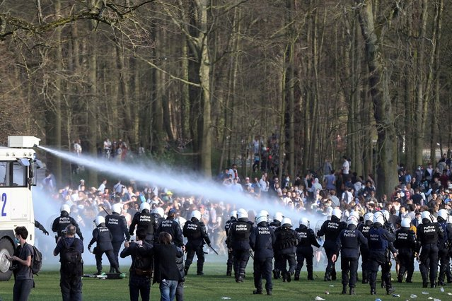 Bystanders and demonstrators are soaked by a Belgian police water canon as police officers surround them at the Bois de la Cambre parc, in Brussels, on April 1, 2021 during a unauthorised rally, for a fake concert announced on social media as an April Fool's Day prank. (Photo by François Walschaerts/AFP Photo)