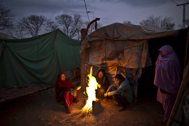 In this Tuesday, February 3, 2015 photo, Pakistani Christian Basharat Bhatti, 43, center, sits with his family gathering around a fire to warm themselves from the evening cold, outside their makeshift tent at a slum home to Christian families on the outskirts Islamabad, Pakistan. The colony home to many Christians who once lived elsewhere in the capital, but fled in fear after a string of blasphemy allegations and killings. (Photo by Muhammed Muheisen/AP Photo)