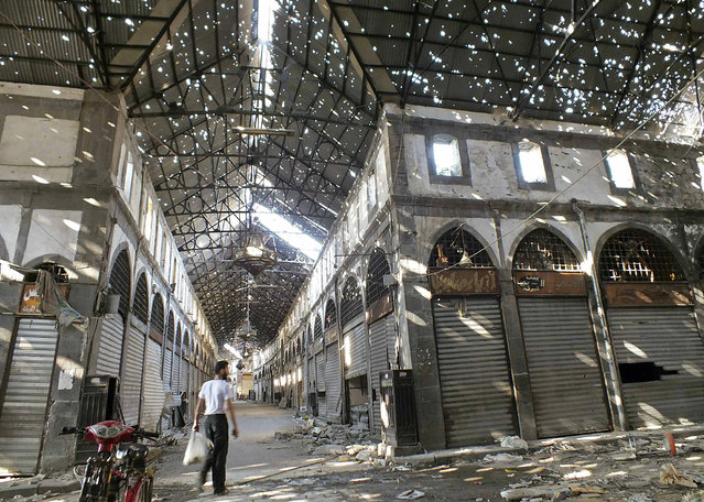A man walks inside the damaged historical old souk of Homs August 19, 2013. (Photo by Yazan Homsy/Reuters)