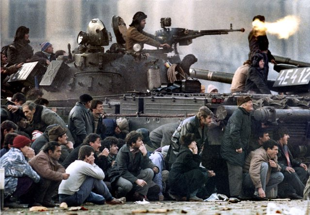Bucharest's residents protect themselves from the crossfire during clashes in the Republican square in Bucharest December in this 23, 1989 file photo. Charles Platiau: On December 22 1989, my mind was still full of memories of covering the fall of the Berlin Wall. I was ready to celebrate Christmas with my family, but the Romanian communist dictator Nicolae Ceausescu changed my plans.  (Photo by Charles Platiau/Reuters)