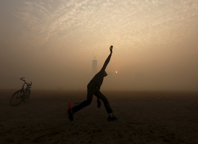 A boy bowls while playing cricket in a public park amidst heavy fog on a cold winter morning in Kolkata, India, December 30, 2015. (Photo by Rupak De Chowdhuri/Reuters)
