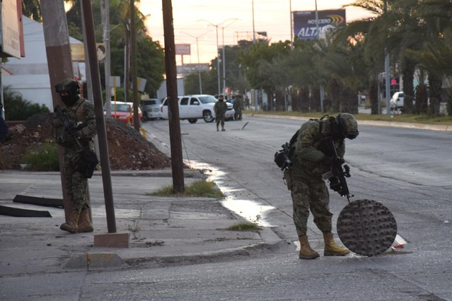 "A Mexican navy marine inspects an open manhole after the recapture of Mexico's most wanted drug lord, Joaquin ""El Chapo"" Guzman in the city of Los Mochis, Mexico, Friday, January 8, 2016. The world's most-wanted drug lord was captured for a third time, as Mexican marines staged heavily-armed raids that caught Guzman six months after he escaped from a maximum security prison. (Photo by Kiko Guerrero via AP Photo/El Debate)"